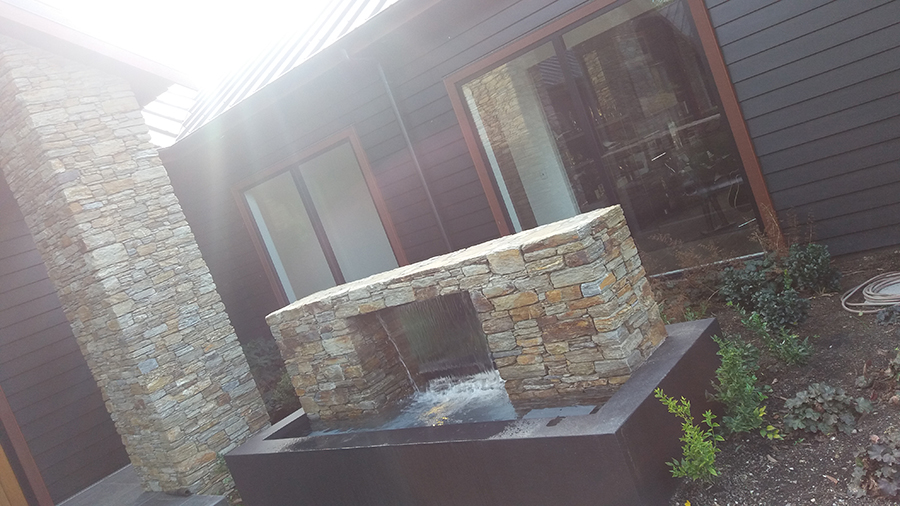 Water Feature Statement Piece with landscaping and garden beside